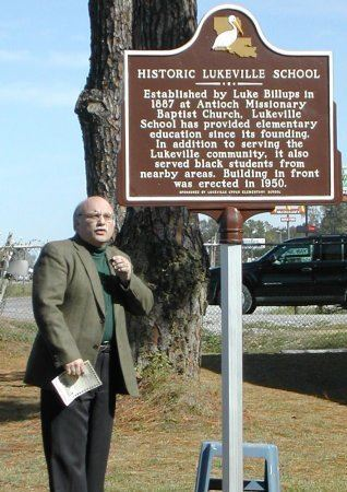 Man talking in front of the historical marker