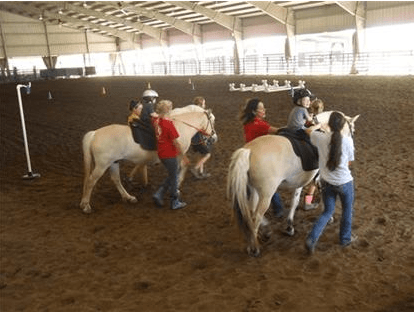 Children riding horses with the help of GaitWay employees